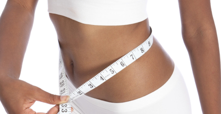 Fit torso of black woman checking diet weight loss